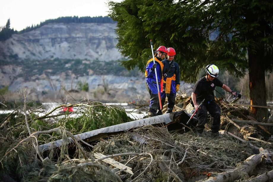 Rescue workers make their way through debris. Photo: JOSHUA TRUJILLO, SEATTLEPI.COM / SEATTLEPI.COM
