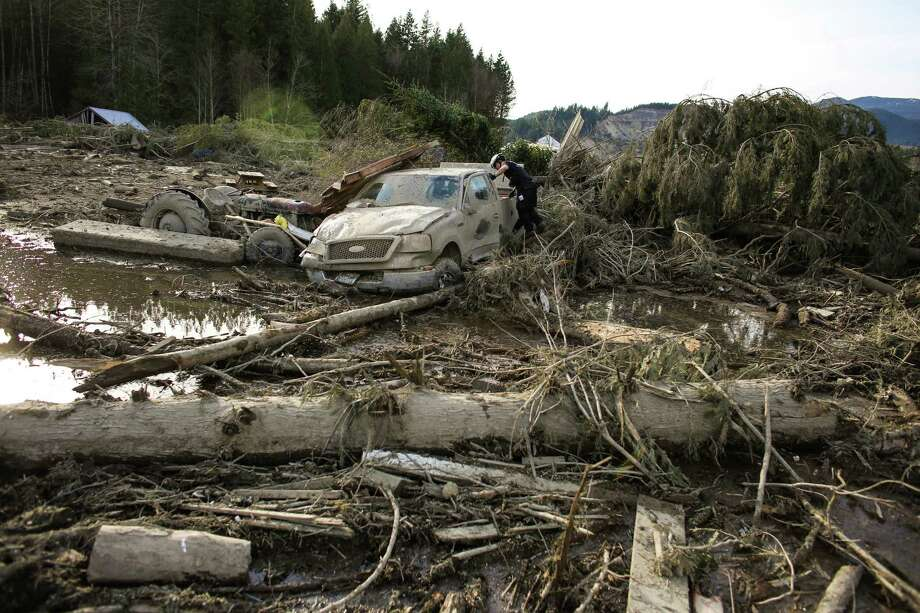 A rescue worker searches a vehicle in the wreckage of homes and lives destroyed by a mudslide near Oso, Wash. Photo: JOSHUA TRUJILLO, SEATTLEPI.COM / SEATTLEPI.COM
