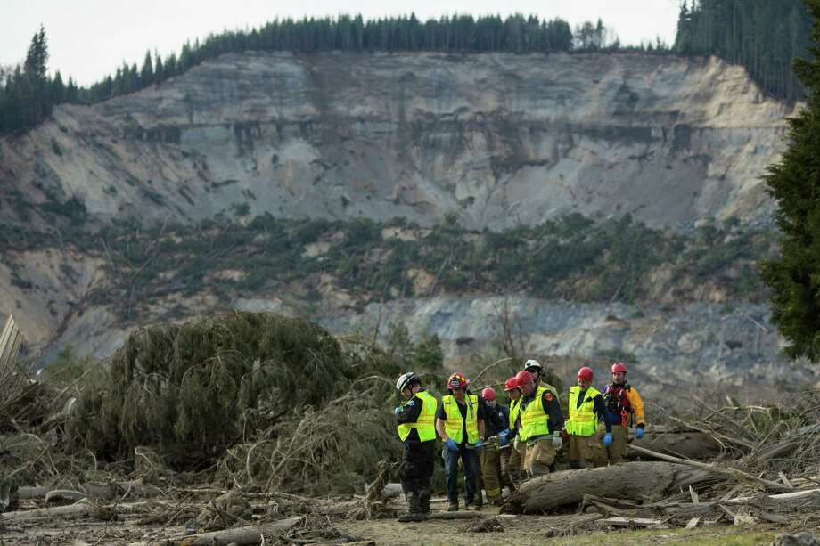 Rescue workers remove one of a number of bodies from the wreckage of homes and lives destroyed by the mudslide near Oso, Wash. Photo: JOSHUA TRUJILLO, SEATTLEPI.COM / SEATTLEPI.COM