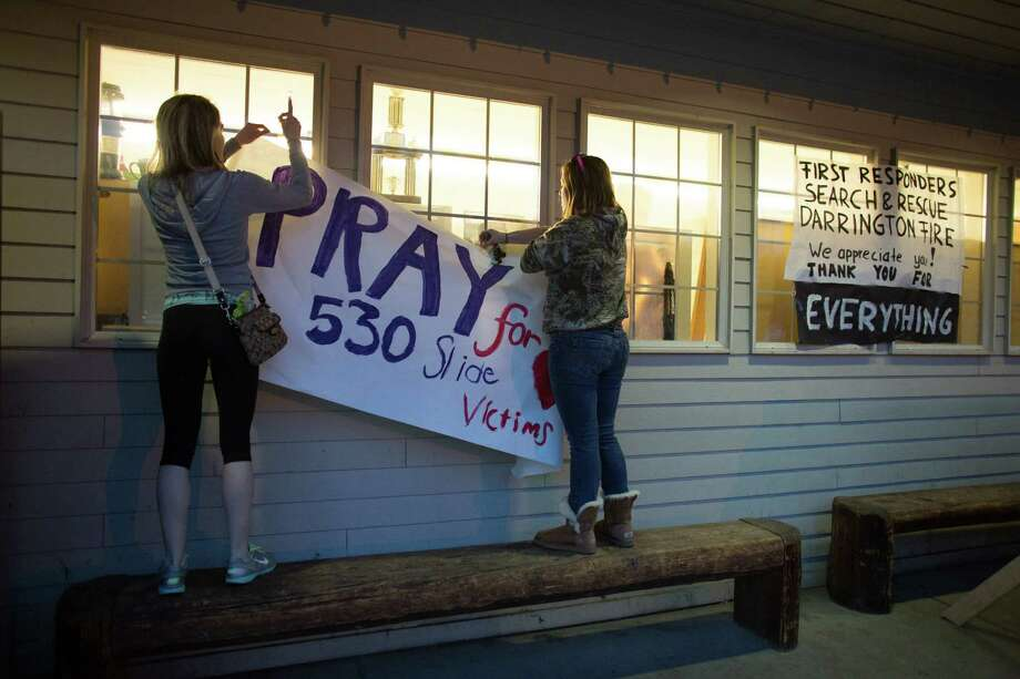 Tayler Hoftell, 17, and Emmarae Reuwsaat, 17, hang a sign in Darrington. In the wake of Saturday's mudslide on Highway 530 in Snohomish County, there have been 175 reports of missing people and the death toll has risen to 14. Photo: JOSHUA TRUJILLO, SEATTLEPI.COM / SEATTLEPI.COM