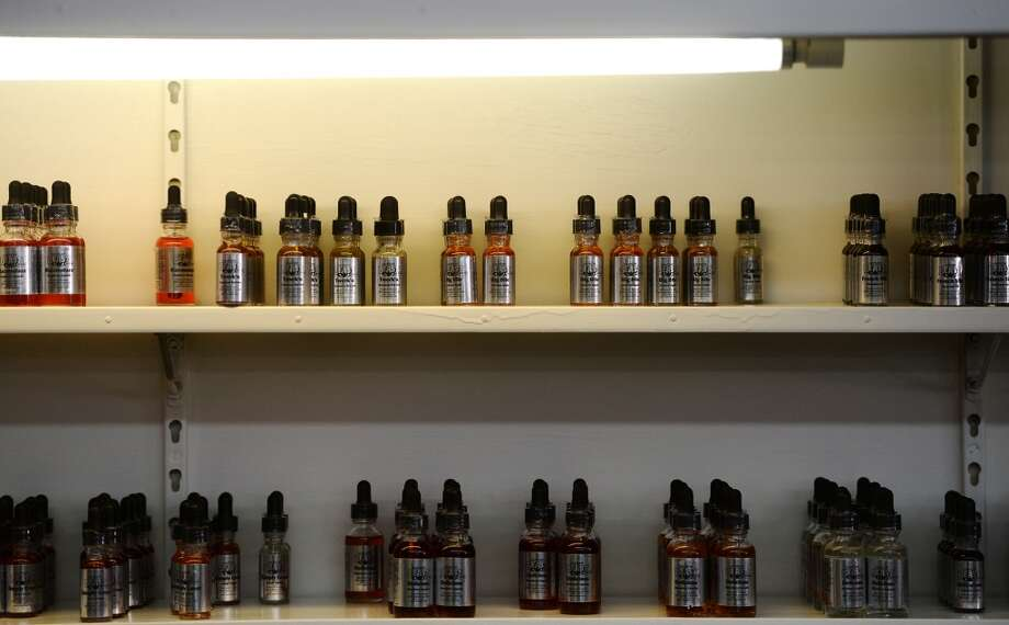 Vapor flavoring lines the shelves at K&C Vapor in Nederland. The new shop caters to fans of e-cigarettes and their variants, including members of the Southeast Texas Steam Knights. Photo taken Wednesday, 3/12/14 Jake Daniels/@JakeD_in_SETX