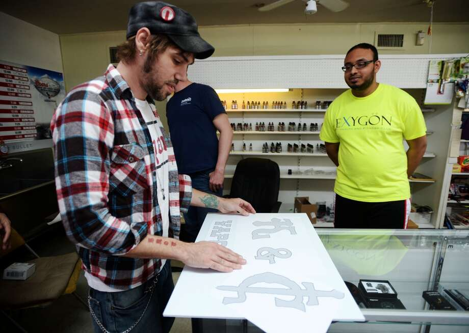 Benjamin Tanner, left, spreads out his design for the K&C Vapor logo for co-owners Chase Stark, background center, and Kashan Khan, right, on Wednesday. The new shop in Nederland caters to fans of e-cigarettes and their variants, including members of the Southeast Texas Steam Knights. Photo taken Wednesday, 3/12/14 Jake Daniels/@JakeD_in_SETX