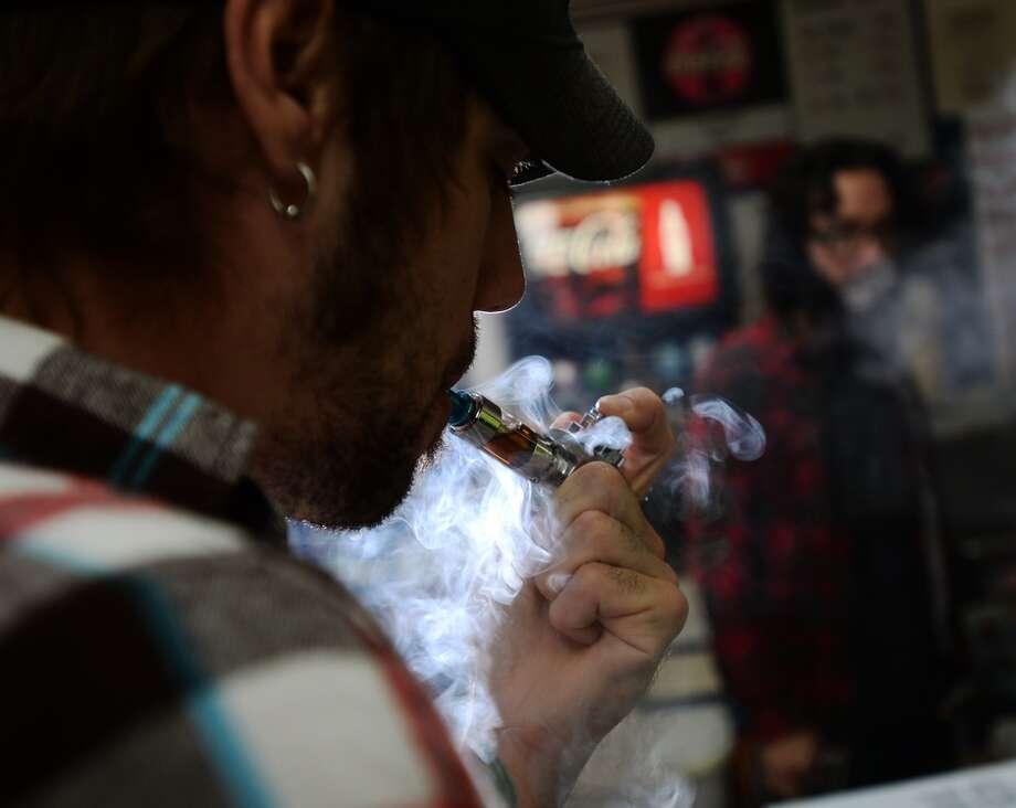 Benjamin Tanner uses a vaping pipe while at K&C Vapor in Nederland on Wednesday. The new shop caters to fans of e-cigarettes and their variants, including members of the Southeast Texas Steam Knights. Photo taken Wednesday, 3/12/14 Jake Daniels/@JakeD_in_SETX