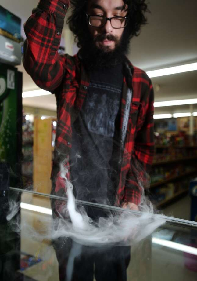 Clayton Coburn watches a small tornado of vapor rise from the countertop at K&C Vapor in Nederland on Wednesday. The new shop caters to fans of e-cigarettes and their variants, including members of the Southeast Texas Steam Knights. Photo taken Wednesday, 3/12/14 Jake Daniels/@JakeD_in_SETX