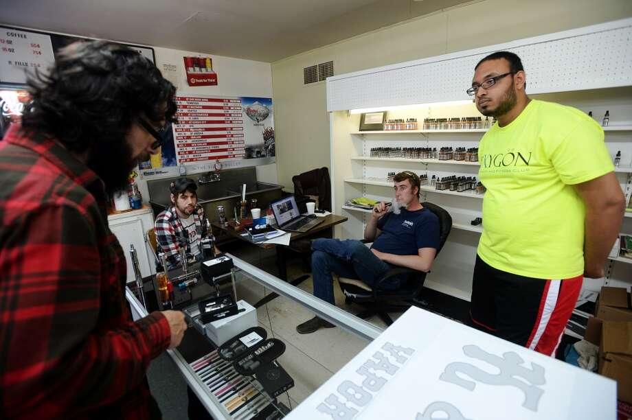 Clayton Coburn, left, looks over vaping accessories while he and Benjamin Tanner, second from left, talk with K&C Vapor co-owners Chase Stark, second from right, and Kashan Khan, right, on Wednesday. The new shop in Nederland caters to fans of e-cigarettes and their variants, including members of the Southeast Texas Steam Knights. Photo taken Wednesday, 3/12/14 Jake Daniels/@JakeD_in_SETX