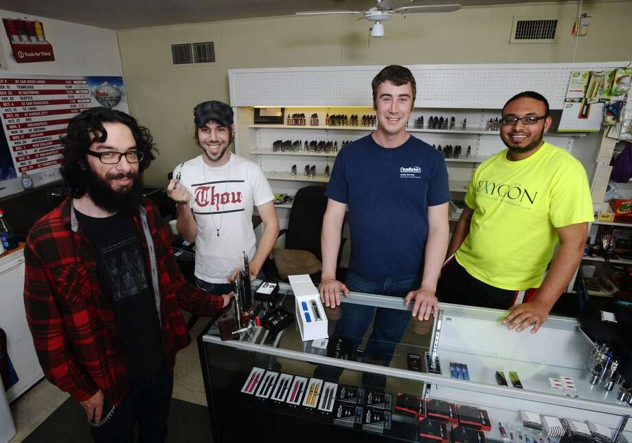Clayton Coburn and Benjamin Tanner, with the Southeast Texas Steam Knights, (left and second from left) pose with Chase Stark and Kashan Khan, co-owners of K&C Vapor, (second from right and right) at the store Wednesday afternoon. K&C Vapor in Nederland caters to fans of e-cigarettes and their variants, including members of the Southeast Texas Steam Knights. Photo taken Wednesday, 3/12/14 Jake Daniels/@JakeD_in_SETX