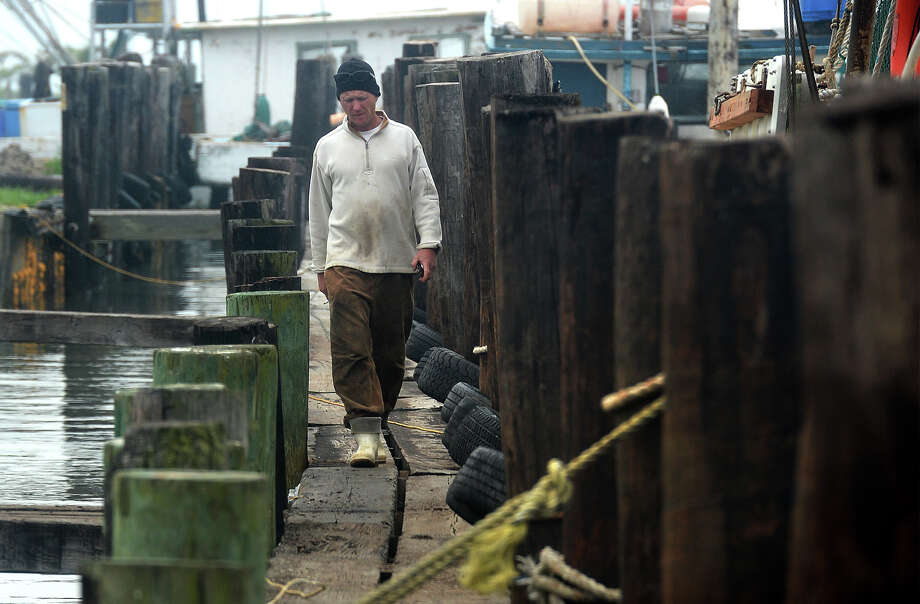 J.T. English, a Bolivar Peninsula fisherman, walks across Milt's Seafood Plant Inc. on Monday. English said he and the other members of the fishing boat Whiskey River and other vessels are grounded due to Saturday's oil spill in the Houston Ship Channel.   Photo taken Monday, March 24, 2014 Guiseppe Barranco/@spotnewsshooter Photo: Guiseppe Barranco, Photo Editor