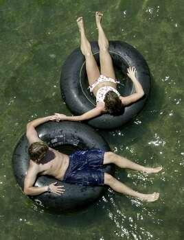 Tubers float the Comal River after it reopened in New Braunfels, Texas, Wednesday afternoon, July 24, 2002. Floating on the Comal and Guadalupe rivers was halted during the July 4th weekend  after heavy rains area caused flooding along both rivers. Most debris has been cleared from the Comal River, but the Guadalupe River remains closed to tubing. Photo: ERIC GAY, AP / AP