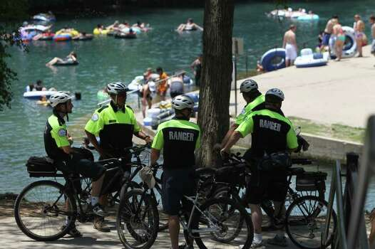 City of New Braunfels Park Rangers gather under a tree as people float by on the Comal River. Photo: SAN ANTONIO EXPRESS-NEWS