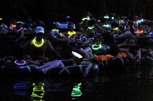 METRO  With lighted necklace glowing in the dark waters of the Comal River, Adventure Club members float together downstream from the Texas Tubes outfitter Saturday night.  NIGHT TUBING ON THE COMAL RIVER FROM TEXAS TUBES   TOM REEL/STAFF   JUNE 17, 2006. Photo: TOM REEL, SAN ANTONIO EXPRESS-NEWS / SAN ANTONIO EXPRESS-NEWS