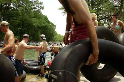 METRO - Jon Myers of College Station loads his tube into the Guadalupe River in Gruene, Texas that packed with young and old for Memorial Day Monday May 29, 2006. KEVIN GEIL/STAFF Photo: KEVIN GEIL, SAN ANTONIO EXPRESS-NEWS / SAN ANTONIO EXPRESS-NEWS