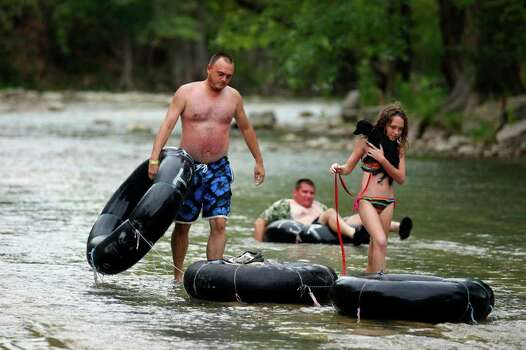 "Tubers Sean Fritz (left) walks with his daughter Britney Fritz as she carries their dog ""Rufus"" on a low section of the Guadalupe River horseshoe Saturday Aug. 13, 2011 in New Braunfels, TX. Photo: EDWARD A. ORNELAS, EDWARD A. ORNELAS / Eaornelas@express-news.net / © SAN ANTONIO EXPRESS-NEWS (NFS)"