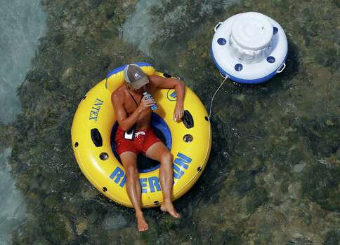 A tuber pulls a cooler along as he floats the Comal River, Monday, Aug. 22, 2011, in New Braunfels, Texas. The New Braunfels City Council is to consider an ordinance banning beer cans and other disposable containers on the Comal River and the Guadalupe River, popular tubing waterways. (AP Photo/Eric Gay) Photo: Eric Gay, Associated Press / AP