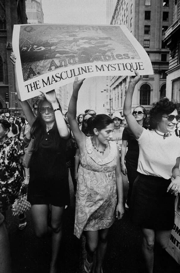 "Writer Gloria Steinem holding up My Lai massacre picture poster with the caption ""THE MASCULINE MYSTIQUE"" as she marches in front line with two other women during women's rights march down 5th Ave. in New York in 1970. Photo: Michael Abramson, Getty Images / Michael Abramson"