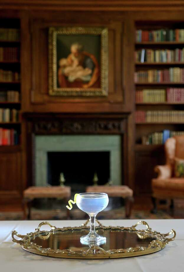 "3/3/14: Martinii, 2 oz gin, 1 oz dry vermouth, 2 dashes orange bitters, stir and served in a coupe glass garnish with lemon twist.The photograph was taken in the library.   The painting in the background is Guido, Saint Joseph and the Christ Child, 1638-40, oil on canvas  at the the Museum of Fine Arts, Houston, The Rienzi Collection, in Houston, Texas. It was a gift by Mr. and Mrs. Harris Masterson III.  Rienzi, the Museum of Fine Arts Houston's museum for European decorative arts, will be the site of a special dinner on April 16 called ""Gin Craze."" The evening's meal courses and cocktails will celebrate the history of gin. It will be prepared by Richard Knight, Benjy Mason (who are partnering in the upcoming Hunky Dory restaurant), Photo: Thomas B. Shea / © 2014 Thomas B. Shea"