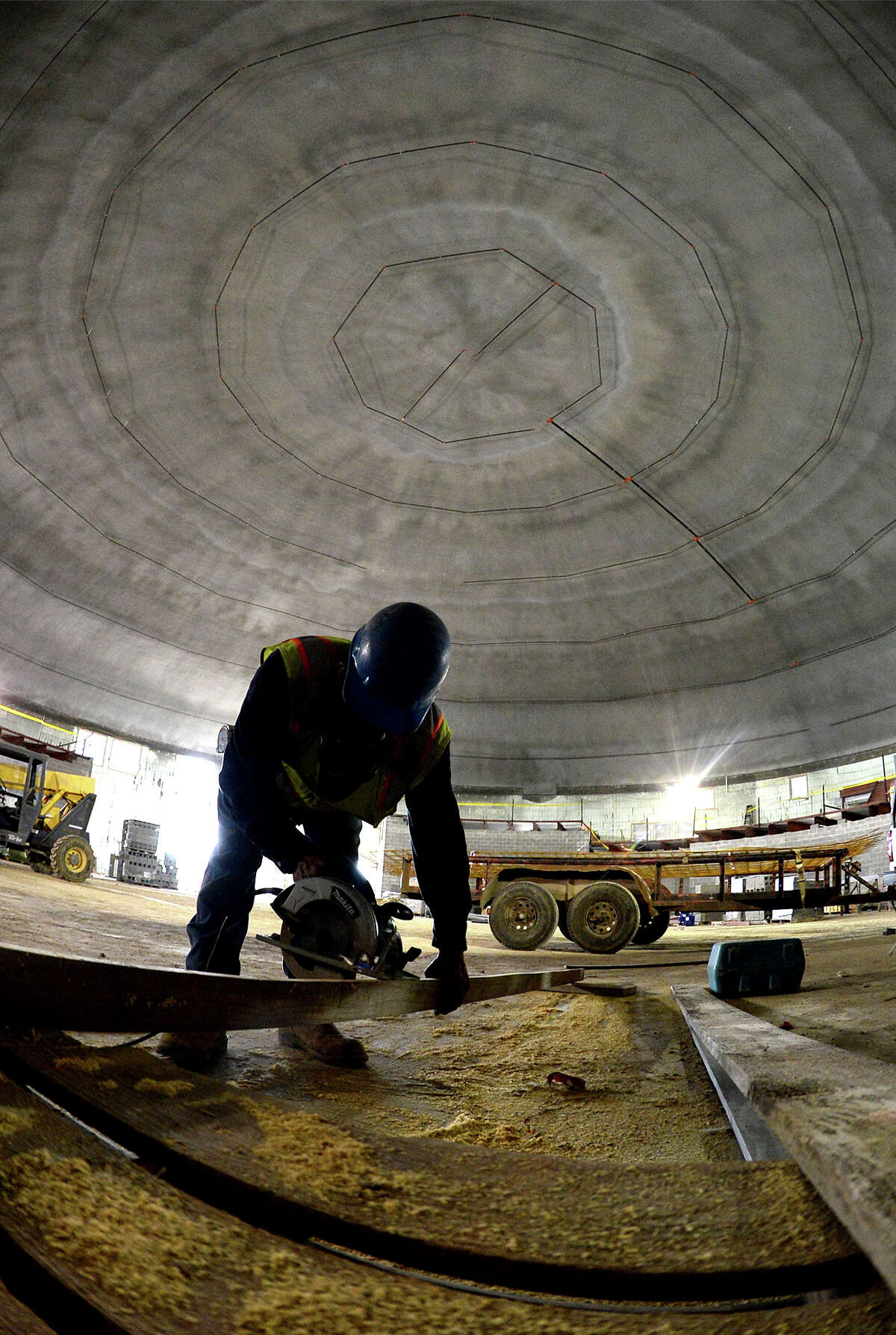 Dario Hernandez cut a plank with a saw at the Performing Arts Center and FEMA Dome being built next to Lumberton High School on March 19, 2014. The dome was completed in 2015 and will serve as a shelter for first responders during disaster situations.