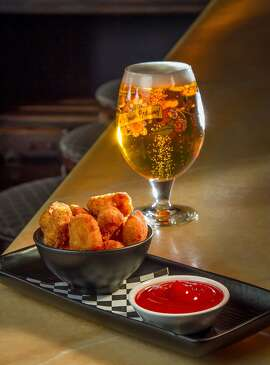 The Gourmet Tots with a Pilsner Urquell at Noir Lounge, Calif., is seen on Wednesday, March 19th, 2014.