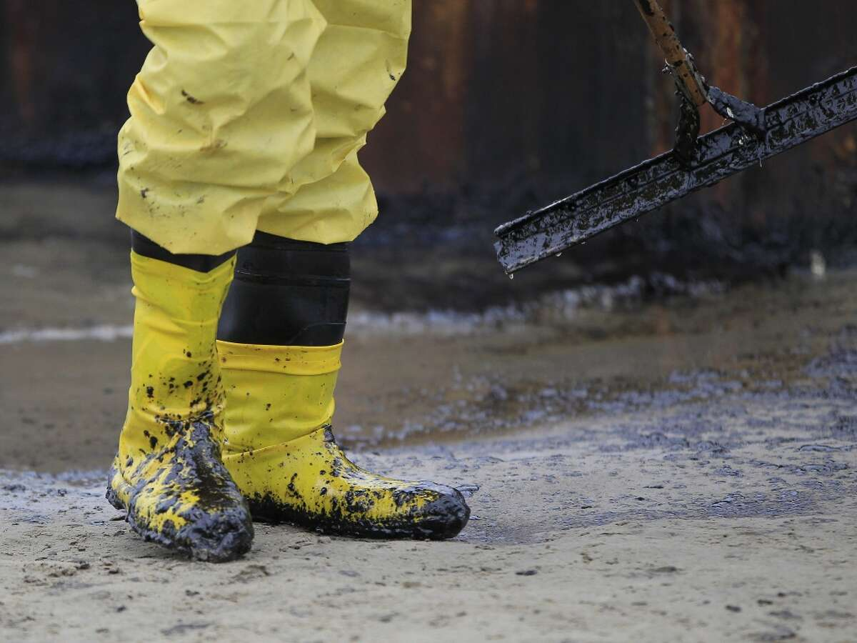 A worker gathers oil that spilled onto the sands of the Texas City dike at the site of the wrecked barge that leaked fuel into the Houston Ship Channel, Monday, March 24, 2014, in Texas City. Thousands of gallons of tar-like oil spilled into the major U.S. shipping channel after a barge ran into a ship Saturday.
