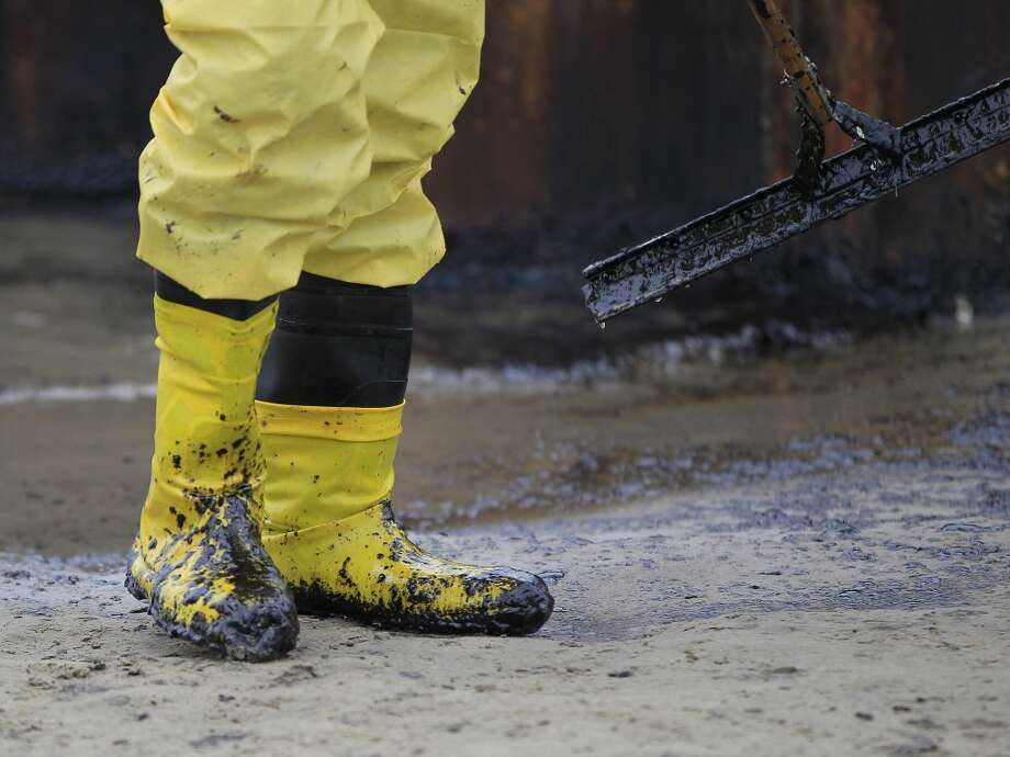 A worker gathers oil that spilled onto the sands of the Texas City dike at the site of the wrecked barge that leaked fuel into the Houston Ship Channel, Monday, March 24, 2014, in Texas City. Thousands of gallons of tar-like oil spilled into the major U.S. shipping channel after a barge ran into a ship Saturday. Photo: Karen Warren, Associated Press