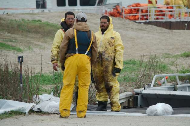 Heavy fuel oil soils the protective suits worn by clean up workers during a clean up effort, Monday, March