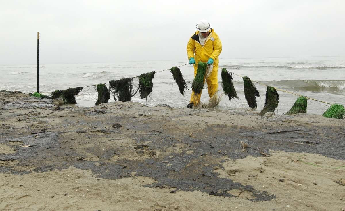Chad Smith, with Garner Environmental Services, moves an oil absorbent skirt back into the surf ,Monday March 24, 2014, on East Beach in Galveston, Texas. Crews were deployed Monday morning to begin cleaning up the heavy fuel oil spilled from a barge over the weekend.