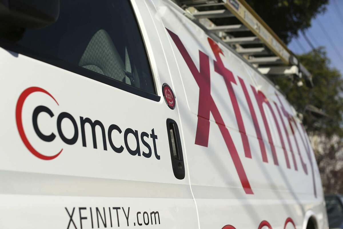 A Comcast sign is shown on the side of a vehicle in San Francisco, California in this file photo taken February 13, 2014. Comcast will formally request an FCC review of a $45.2 billion Time Warner Cable deal later in March. The combined company will cover just under 30 percent of the U.S. pay television video market and about 33 percent of the high-speed Internet market, according to MoffettNathanson Research. REUTERS/Robert Galbraith/Files (UNITED STATES - Tags: MEDIA BUSINESS)