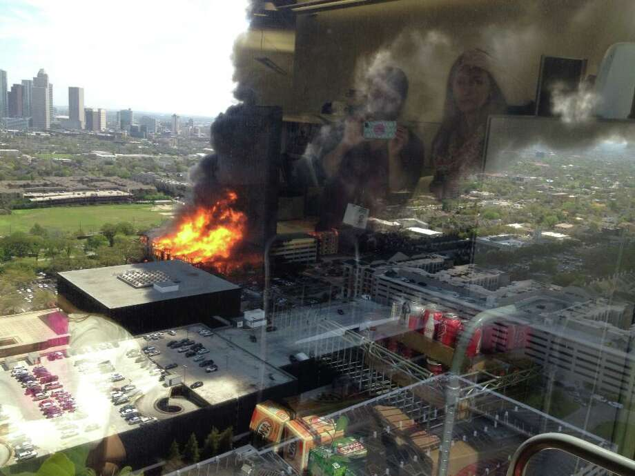Firefighters are battling a large blaze Tuesday afternoon at an  apartment building just west of downtown. The fire broke out about 12:30  p.m. on West Dallas near Montrose. Photo: Rusha Desai Jayasuriya, Special To The Houston Chronicle