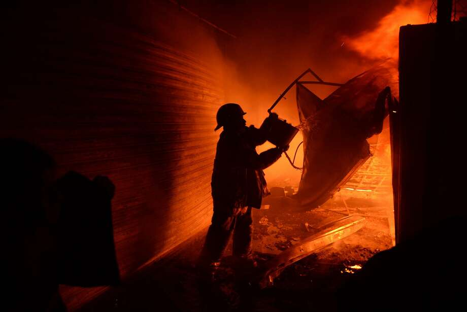 """Farmers drinking away their sorrows no doubt: A firefighter tries to douse a fire at La   Terminal market in Guatemala City. """"The disaster left four injured, 50 intoxicated and at   least 400 stalls destroyed,"""" according to the AFP/Getty caption. Photo: Johan Ordonez, AFP/Getty Images"""