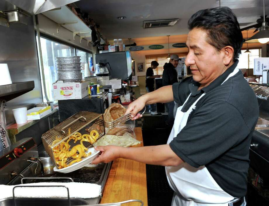 Curly fries are a popular item at the Sycamore Drive-In Restaurant in Bethel, Conn. Marcelo Tenempaguay is the man behind the grill Tuesday, March 25, 2014. Photo: Carol Kaliff / The News-Times