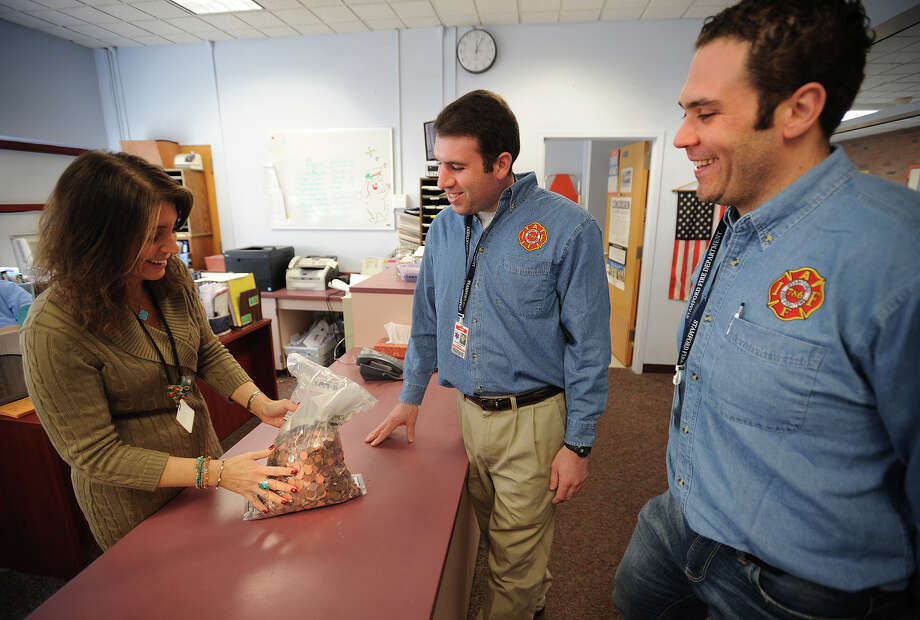 From left; Newfield School Principal Lisa Saba-Price, left, hands a bag of student collected coins to Stamford firefighters Brian Teitelbaum and Nick Tamburro as part of a fund raising effort for a new playground in memory of one of the Sandy Hook shooting victims on Tuesday, March 25, 2014. Photo: Brian A. Pounds / Connecticut Post