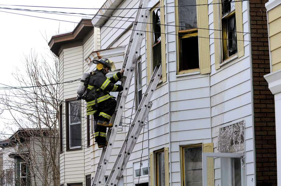 An Albany firefighter climbs down a ladder after responding to a fire at 296 Sheridan Ave. on Tuesday, March 25, 2014, in Albany, N.Y. (Cindy Schultz / Times Union) Photo: Cindy Schultz