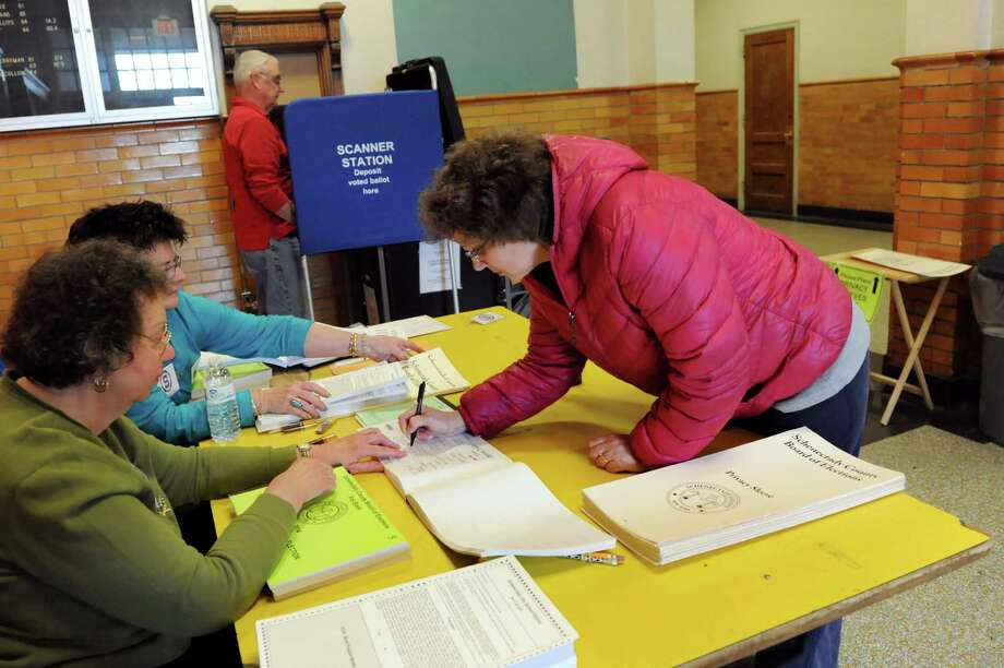 Kim Miller, right, signs in to vote on a school referendum on Tuesday, March 25, 2014, at Mont Pleasant Middle School in Schenectady, N.Y. Election inspectors, from left, are Helen Saunders, Donna Foley and Tom McKone. (Cindy Schultz / Times Union) Photo: Cindy Schultz / 00026201A