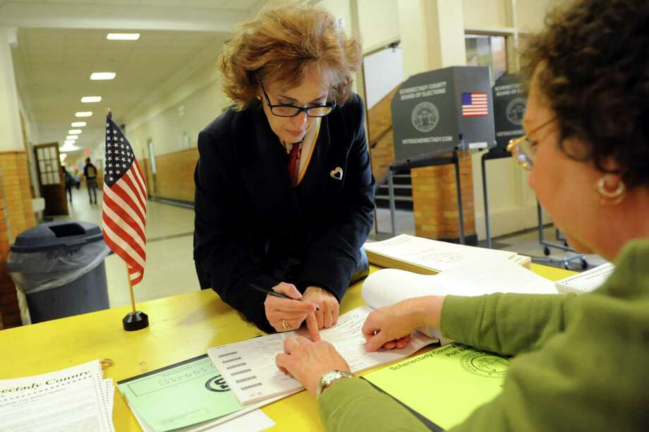 Patricia Ann Smith, vice president of the Mont Pleasant Neighborhood Assoc., center, signs in to vote on a school referendum on Tuesday, March 25, 2014, at Mont Pleasant Middle School in Schenectady, N.Y. Election inspectors Helen Saunders, right, assists. (Cindy Schultz / Times Union) Photo: Cindy Schultz / 00026201A