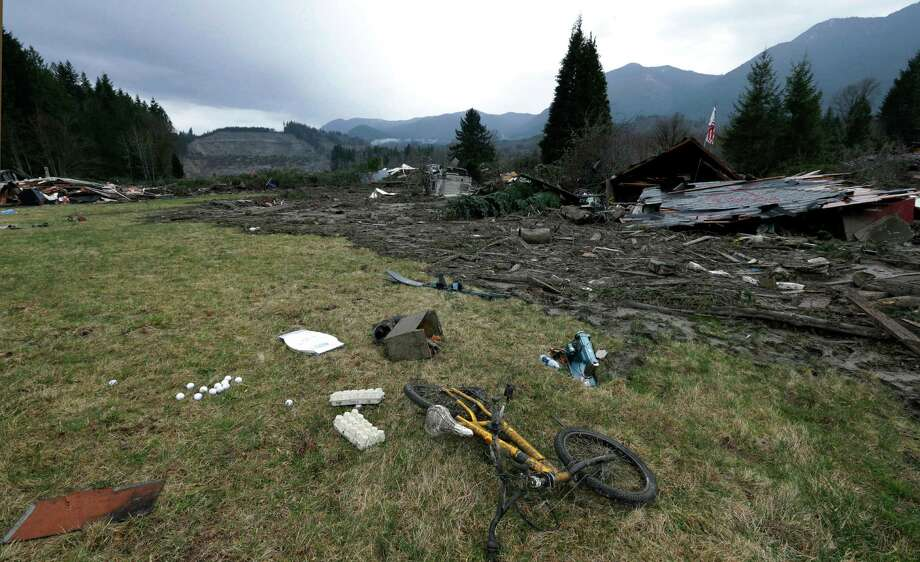 A child's bicycle is with other remains at the edge of the scene of a deadly mudslide from the barren hillside beyond Tuesday in Oso. The 1-square-mile slide hit in a rural area about 55 miles northeast of Seattle on Saturday.  Photo: Elaine Thompson, Associated Press / AP2014