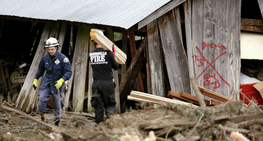 Searchers move lumber to help stabilize a destroyed structure before searching it Tuesday in Oso.  Photo: Elaine Thompson, Associated Press / AP