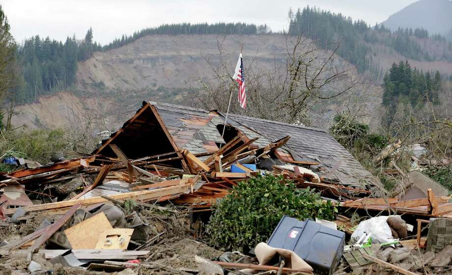 A flag sticks on Tuesday out of a hole in a demolished home near where a deadly mudslide from the hill behind that happened several days earlier ended. Photo: Elaine Thompson, Associated Press / AP2014
