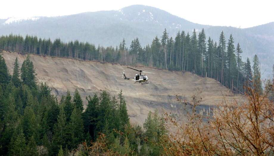 A helicopter flies past the area where a deadly mudslide hit on Saturday, Tuesday in Arlington. Photo: Elaine Thompson, Associated Press / AP2014