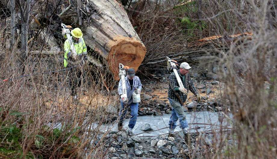 Volunteers with chainsaws cross a small creek as they head to the scene of a deadly mudslide Tuesday in Oso. The 1-square-mile slide that hit in a rural area about 55 miles northeast of Seattle on Saturday.  Photo: Elaine Thompson, Associated Press / AP2014