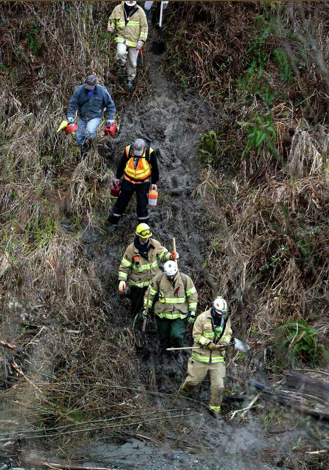 Volunteers and firefighters with chainsaws and hand tools hike down a rugged path toward the scene of a deadly mudslide Tuesday in Oso.  Photo: Elaine Thompson, Associated Press / AP2014