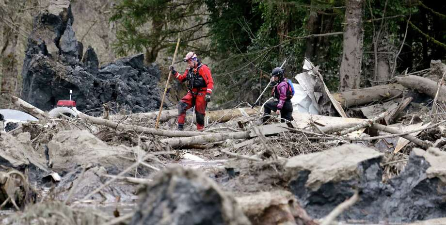 Searchers look through debris from a deadly mudslide Tuesday in Oso. The 1-square-mile slide that hit in a rural area about 55 miles northeast of Seattle on Saturday.  Photo: Elaine Thompson, Associated Press / AP2014