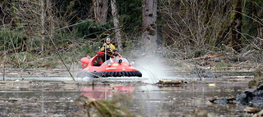 Searchers work from aboard a hovercraft while looking through debris from a mudslide Tuesday in Oso. The 1-square-mile slide that hit in a rural area about 55 miles northeast of Seattle on Saturday.  Photo: Elaine Thompson, Associated Press / AP2014