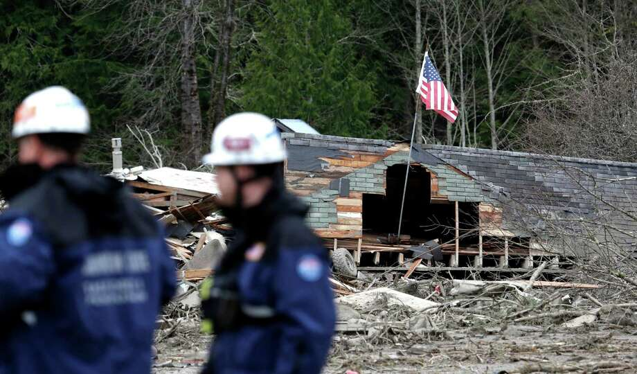 Searchers stand in view of several destroyed homes as they wait to begin looking through the debris of a mudslide Tuesday in Oso. The 1-square-mile slide that hit in a rural area about 55 miles northeast of Seattle on Saturday.  Photo: Elaine Thompson, Associated Press / AP2014