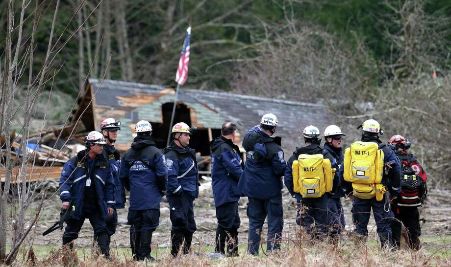 Searchers prepare to begin looking through a debris field as a destroyed home stands behind, Tuesday in Oso. The 1-square-mile slide that hit in a rural area about 55 miles northeast of Seattle on Saturday.  Photo: Elaine Thompson, Associated Press / AP