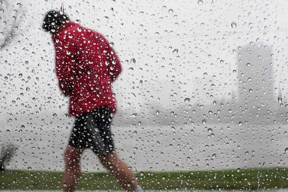 A jogger ducks raindrops near Lake Merritt in Oakland on Tuesday. Photo: SF Gate / Douglas Zimmerman