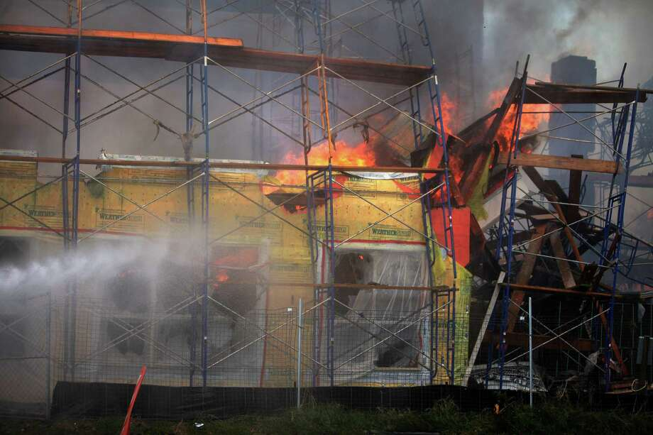An apartment construction site goes up in flames as Houston Fire Department attempts to extinguish the blaze at the corner of Marconi St. and Dallas Ave. on March 25, 2014, in Houston, Tx. Photo: Mayra Beltran, Houston Chronicle / © 2014 Houston Chronicle