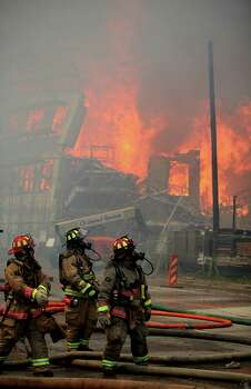 Firefighter see a second building catch fire as they attempt to contain a five-alarm fire at a construction site where apartments were being built at the corner of Marconi St. and Dallas Ave. on March 25, 2014, in Houston, Tx. Photo: Mayra Beltran, Houston Chronicle / © 2014 Houston Chronicle