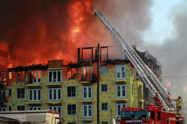 Firefighters attempt to contain a five-alarm fire at an apartment building under construction at the corner of Marconi St. and Dallas Ave. on March 25, 2014, in Houston, Tx. Photo: Mayra Beltran, Houston Chronicle / © 2014 Houston Chronicle