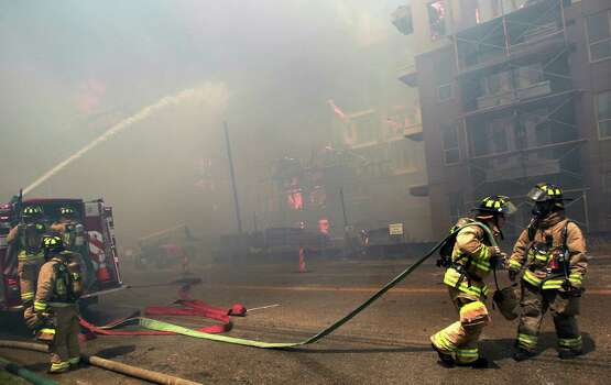 Houston firefighters work to extinguish a five-alarm fire at a construction site Tuesday, March 25, 2014, in Houston. Fire officials said more than 200 emergency personnel were at the scene Tuesday afternoon and were working to protect nearby buildings. (Houston Chronicle, Mayra Beltran)  Photo: Mayra Beltran, Houston Chronicle / Houston Chronicle