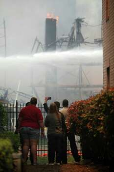 People take photos as Houston firefighters work to extinguish a five-alarm fire at a construction site Tuesday, March 25, 2014, in Houston. Fire officials said more than 200 emergency personnel were at the scene Tuesday afternoon and were working to protect nearby buildings. (Mayra Beltran/Houston Chronicle)  Photo: Mayra Beltran, Houston Chronicle / Houston Chronicle