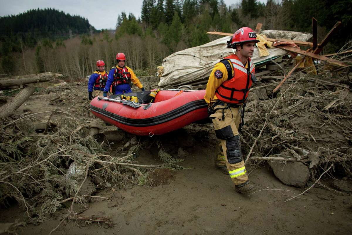 Rescue workers carry a boat into the mudslide debris near Oso, Wash. In the wake of Saturday's mudslide in Snohomish County, there have been over 150 reports of missing people or unaccounted individuals and dozens of bodies found in the debris.